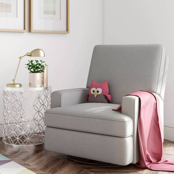 A gray swivel recliner rocking chair