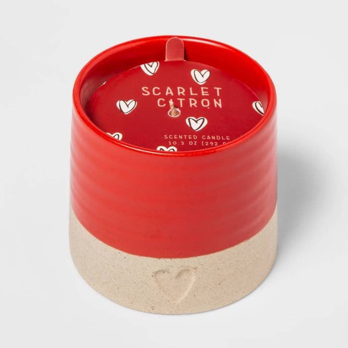 The candle, which comes in a circular ceramic holder that is red on top and beige on the bottom, with a small heart printed in the base