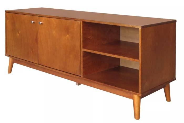 A mid-century modern wooden TV stand with two open shelves on the right and a cabinet on the left