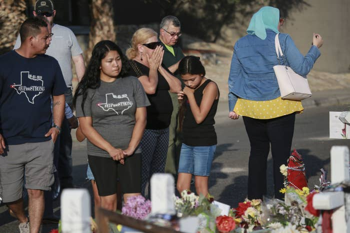 A group of people gathers around a memorial with flowers