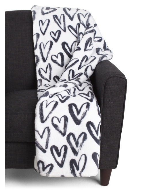 a white throw blanket with black hearts on it