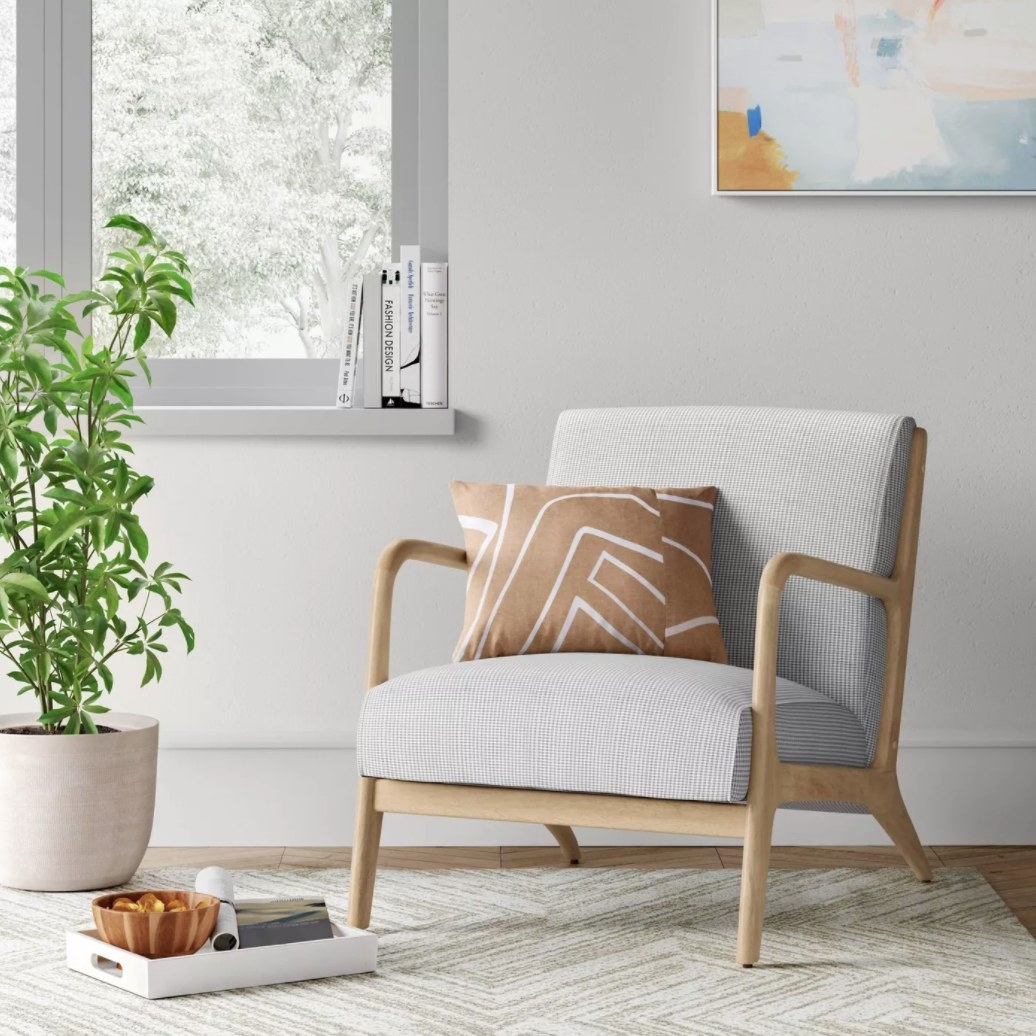 A gray chair with wooden arms and base