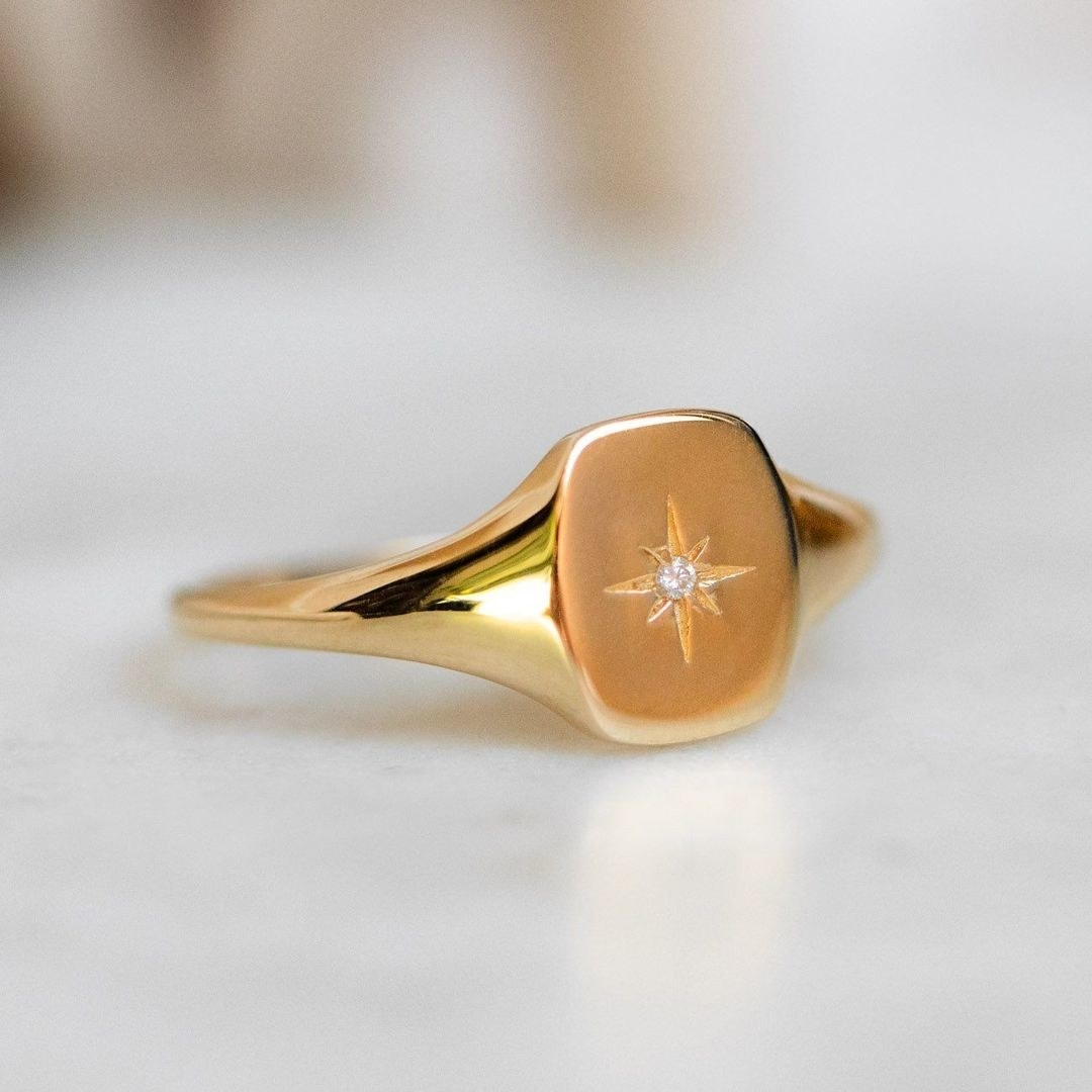a square chunky gold ring with a star in the center with a stone in the middle