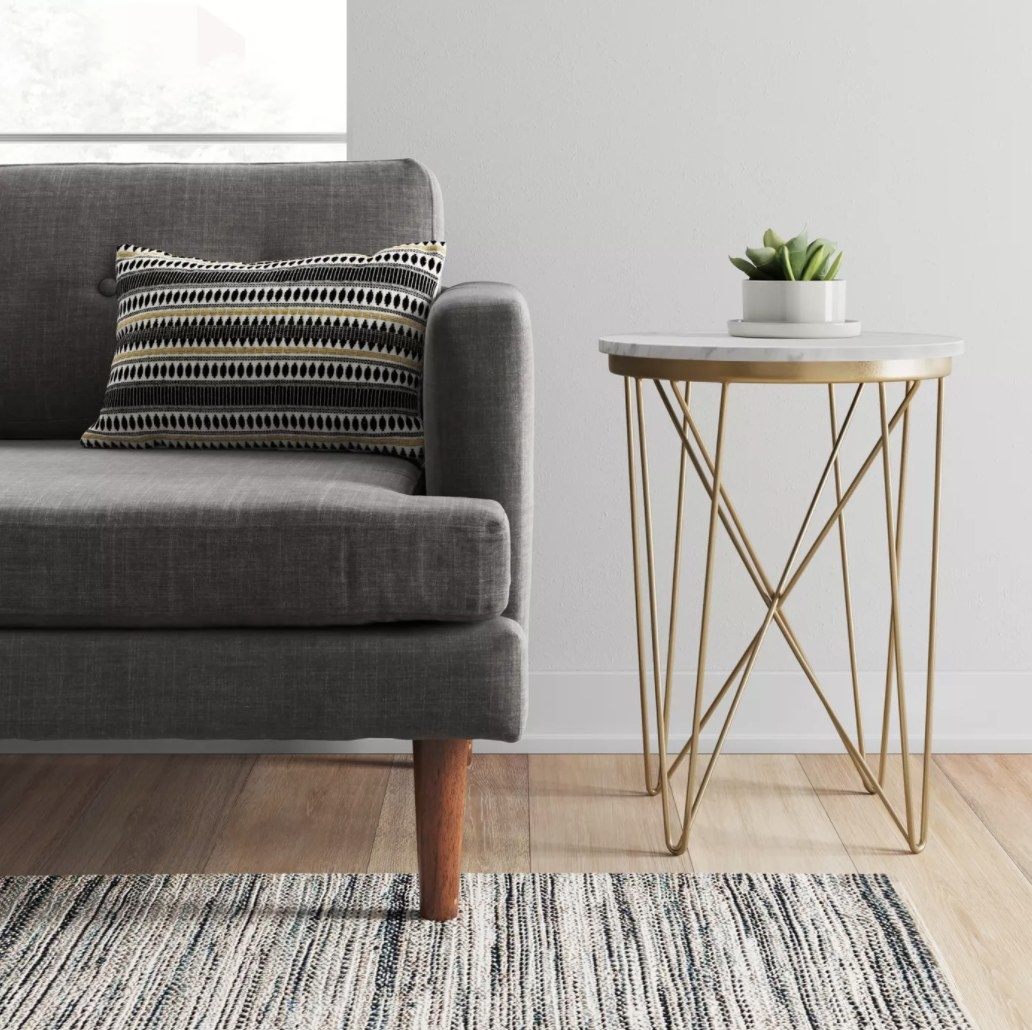 A side table with marble top and gold geometric legs