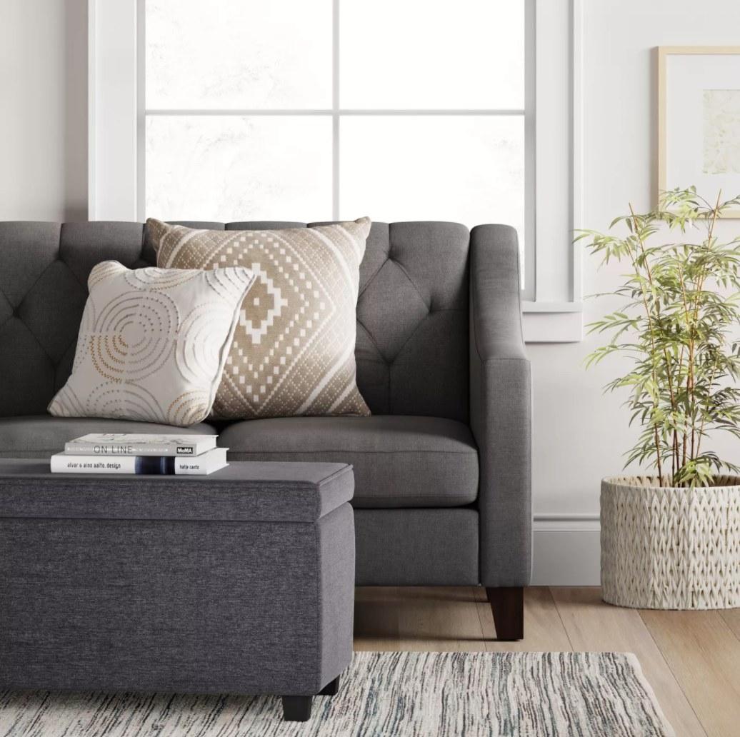 A gray fabric storage ottoman