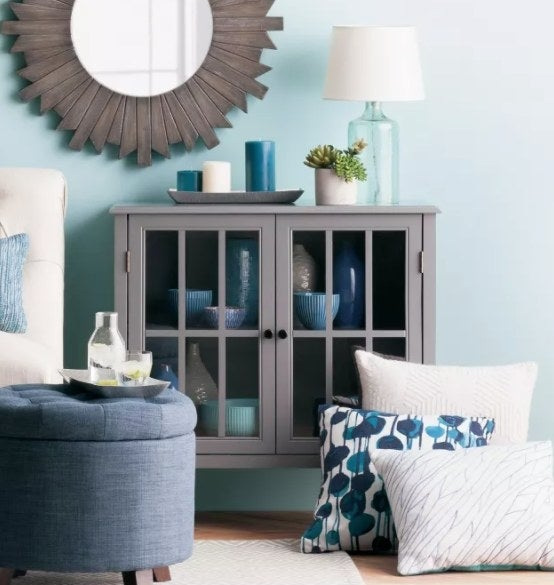 A gray cabinet with glass doors