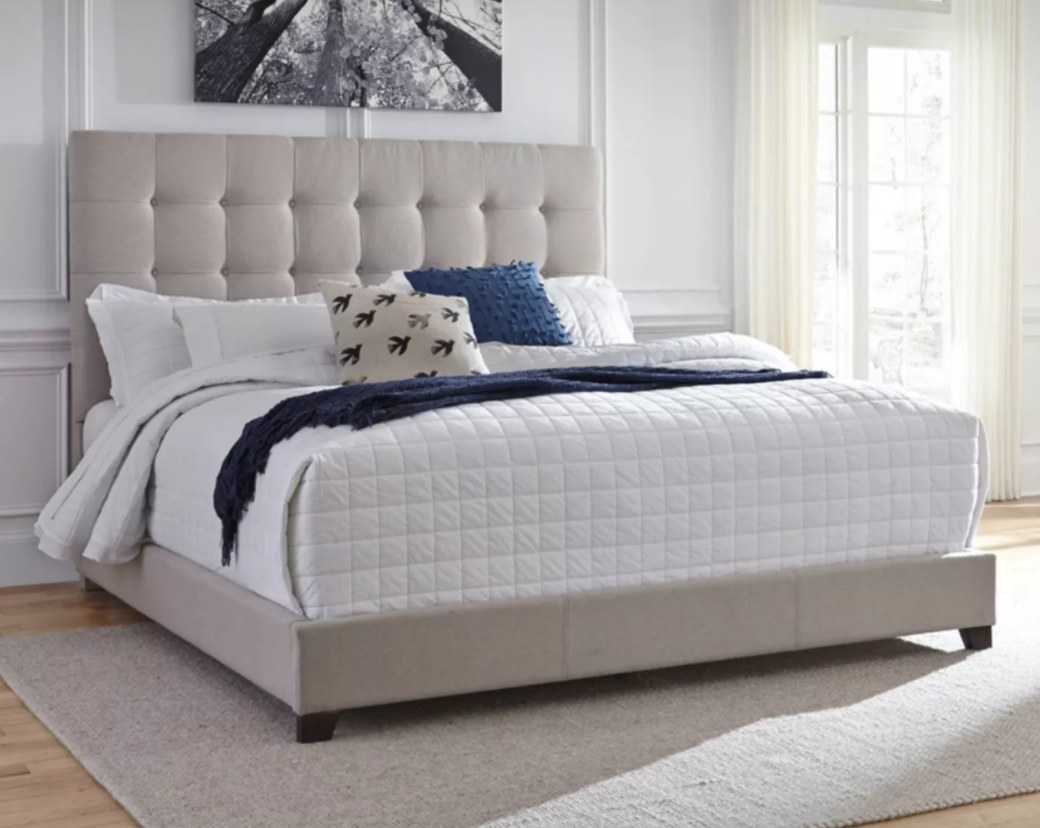 A light gray upholstered bedframe with tufted headboard