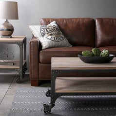 A coffee table with wooden top, lower shelf, metal frame, and caster wheels