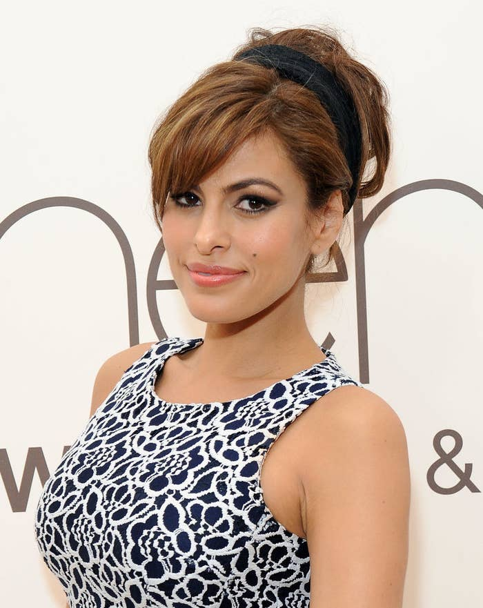 Eva Mendes smiling at a press event wearing a black and white flower dress