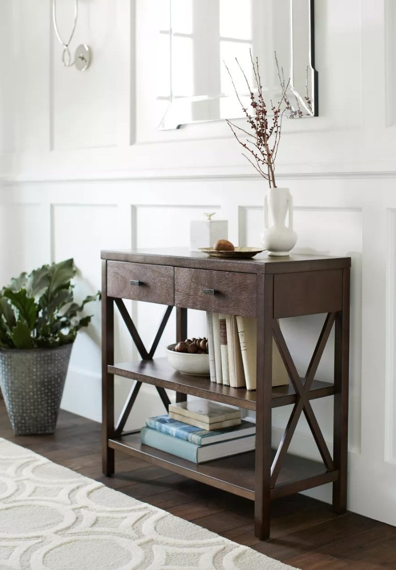 A brown wood console table with two drawers and two lower shelves