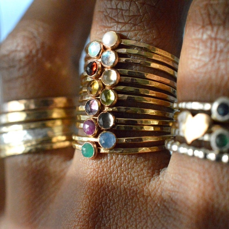close-up of a lot of rings on one person's finger. There are about 10 and they have a skinny gold band with a tiny round birthstone in the center