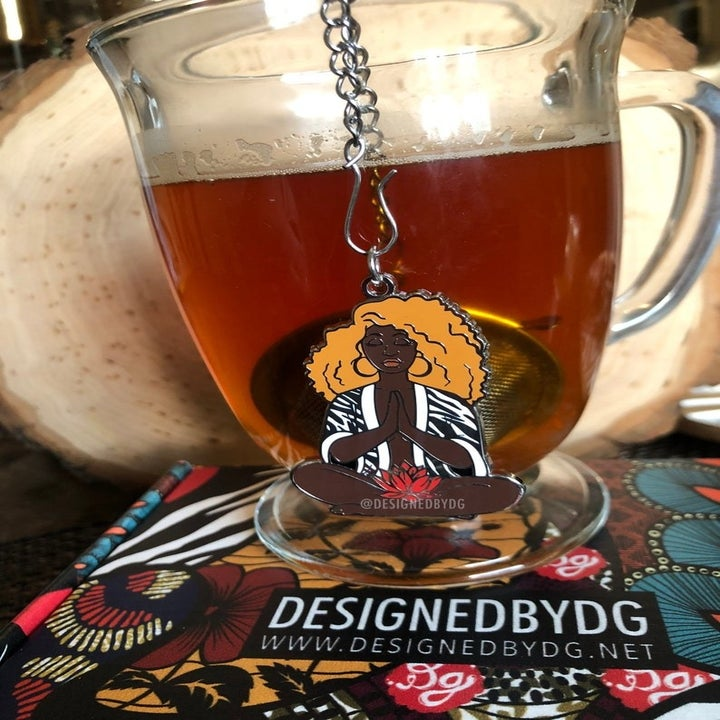 a charm chain on the end of a tea steeper ball and hanging from the side of a clear mug with tea in it. The charm is shaped like a dark-skinned Black woman with big curly hair