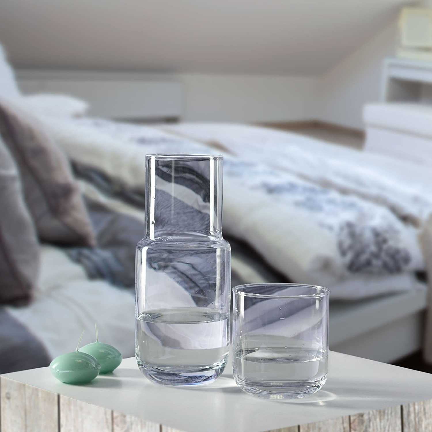 water carafe on bedside table with two candles