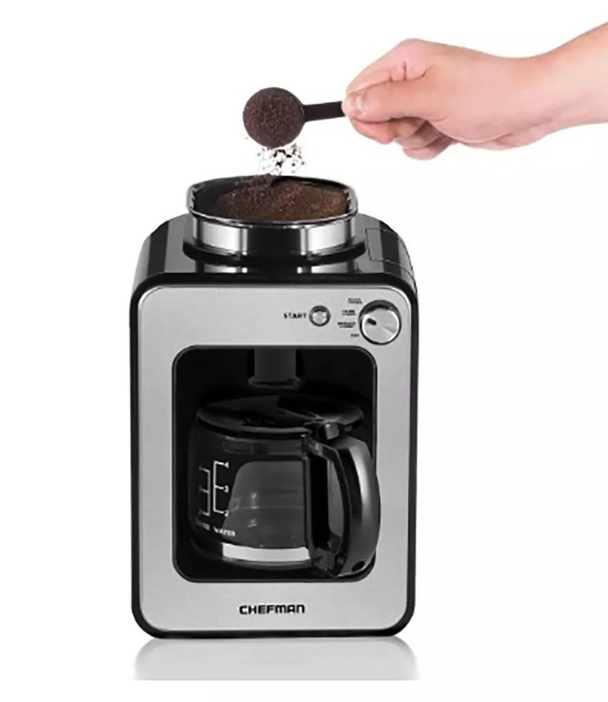 A hand pouring coffee grinds into the top of the Chefman coffee maker