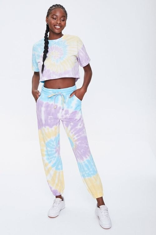 Model wearing the yellow, lavender, and blue sweatpants with matching tee