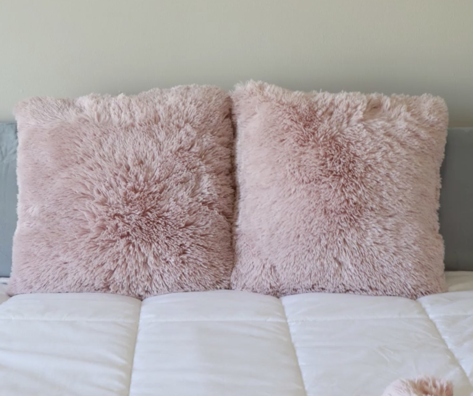 Two blush pink faux fur throw pillows on a bed