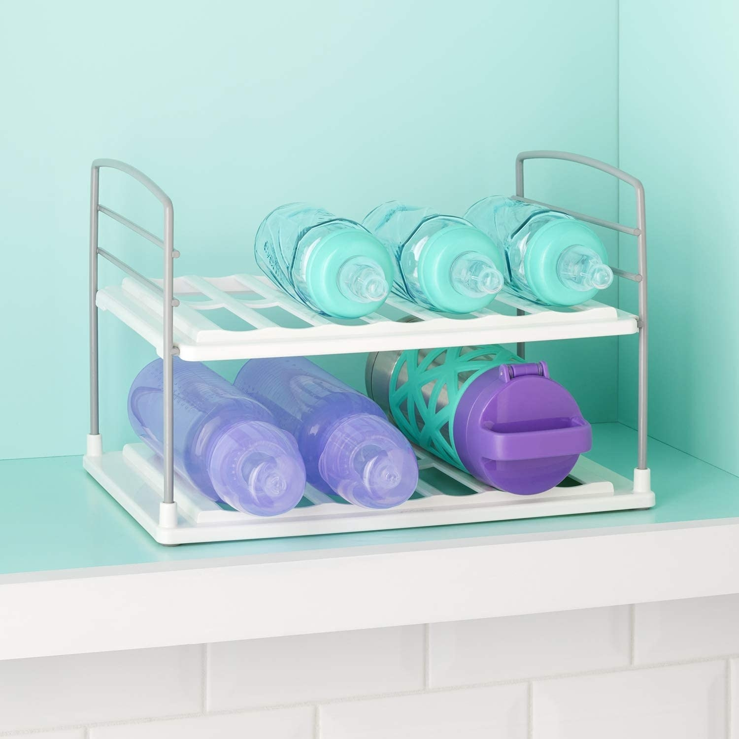 A grooved water bottle rack inside a kitchen cabinet