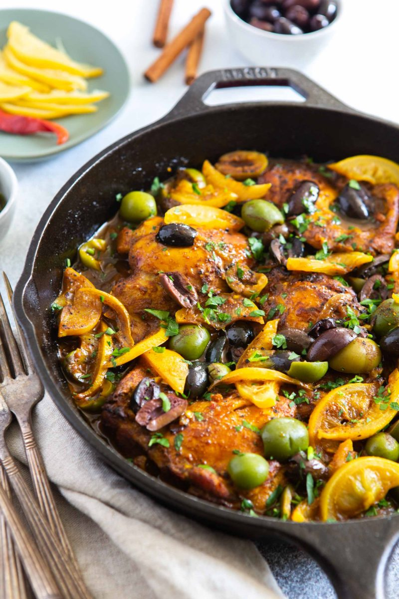 A skillet of chicken with olives and preserved lemons.