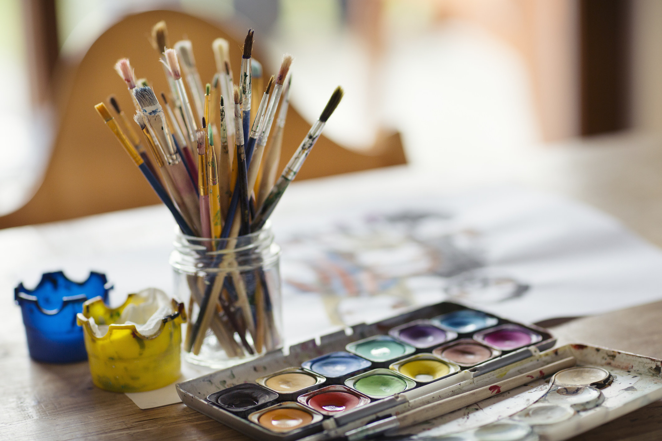 Paints and a set of paint brushes on a table