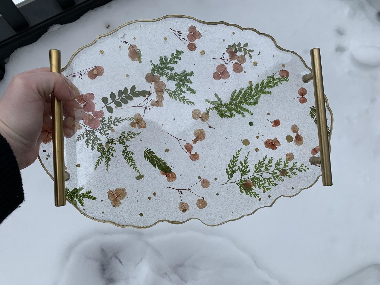 A clear resin tray with gold handles and pink flowers and green leaves designed throughout