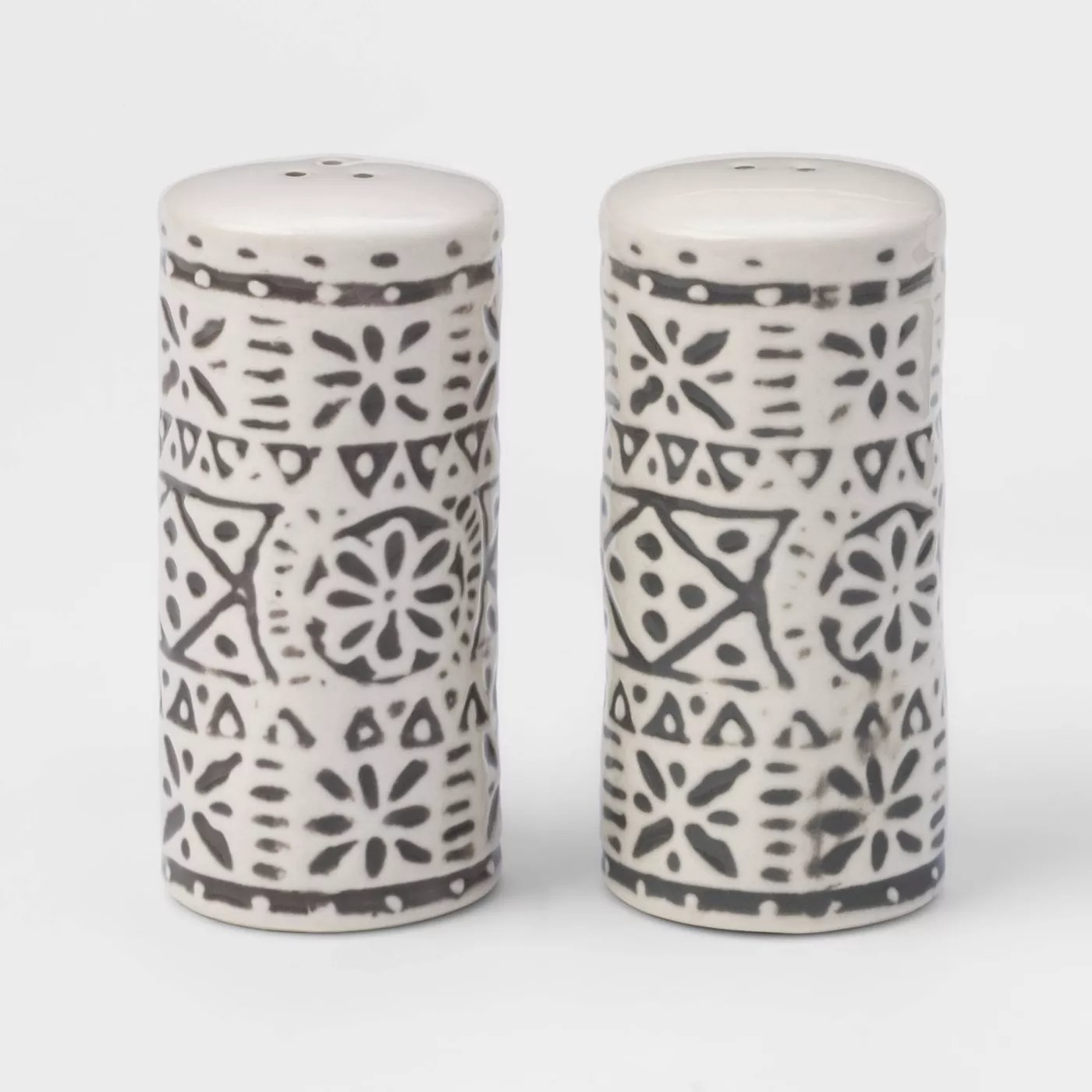 The salt and pepper shakers, standing next to each other