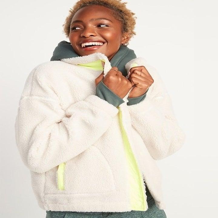 model wearing white sherpa jacket with yellow zipper