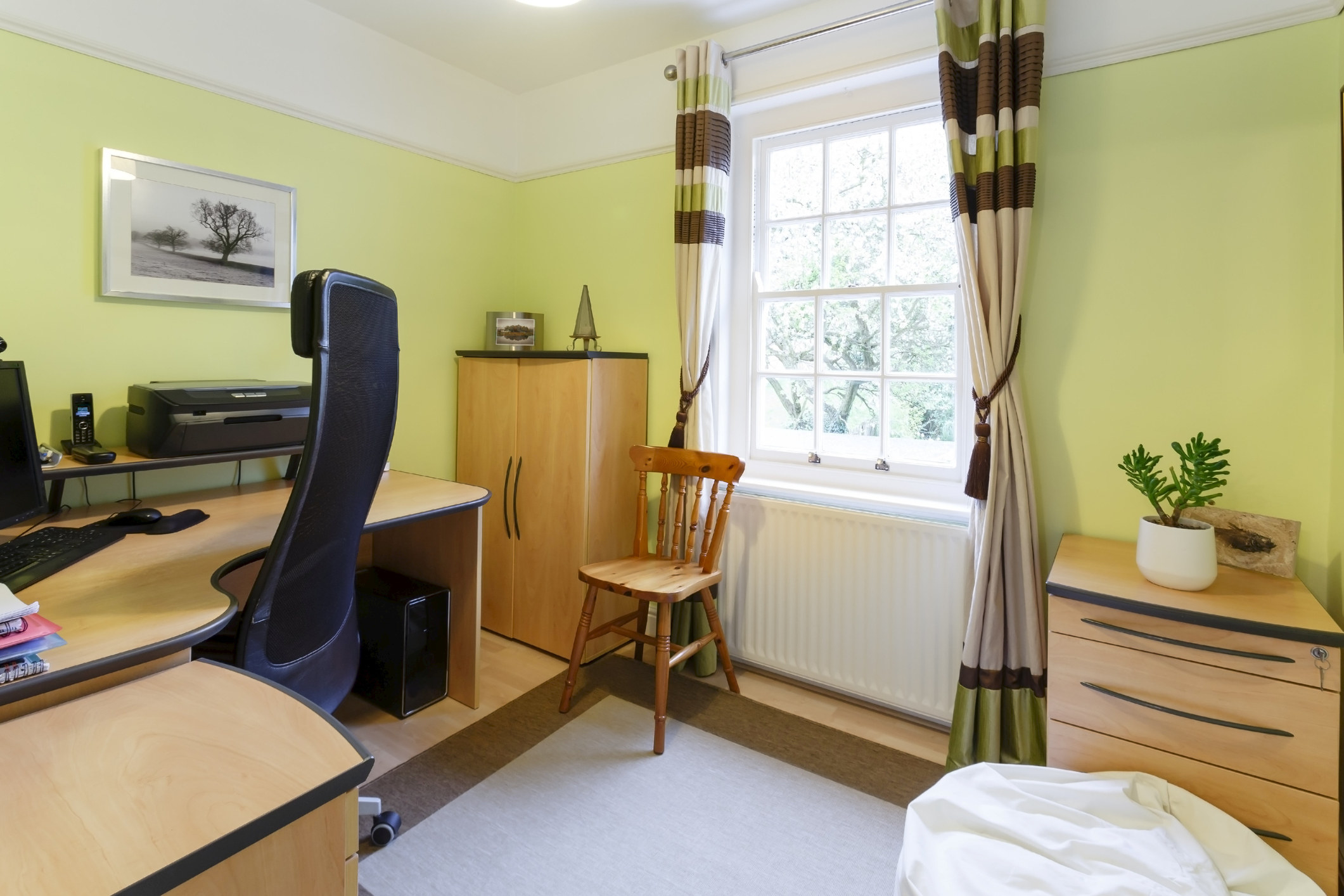 A bedroom with a desk, dresser, curtains revealing a window, and chair