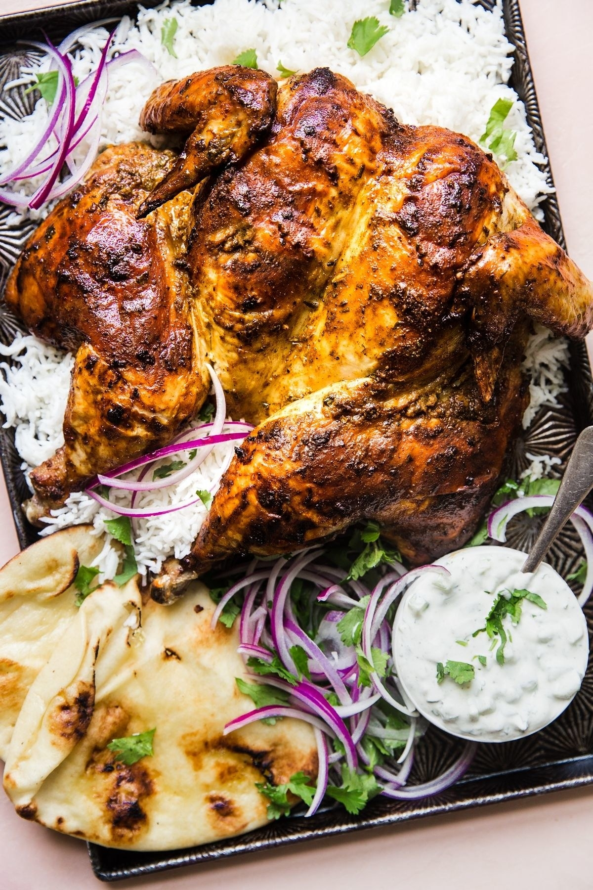 Roasted tandoori chicken with naan, sliced red onion, and tzatziki.