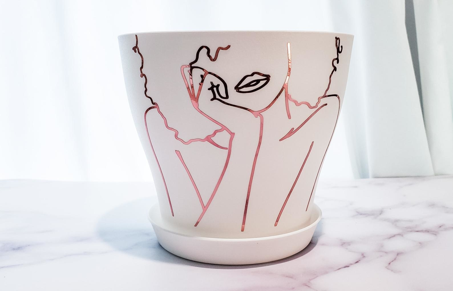 A white plastic planter with line vinyl design in rose gold of a person with their head resting in their hands