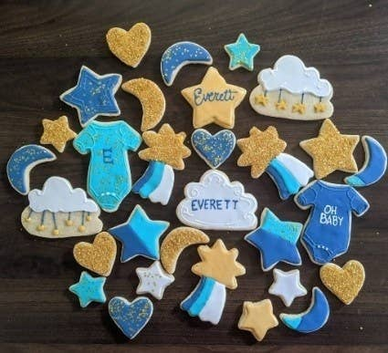A community member showing sugar cookies decorated to be a baby boy theme