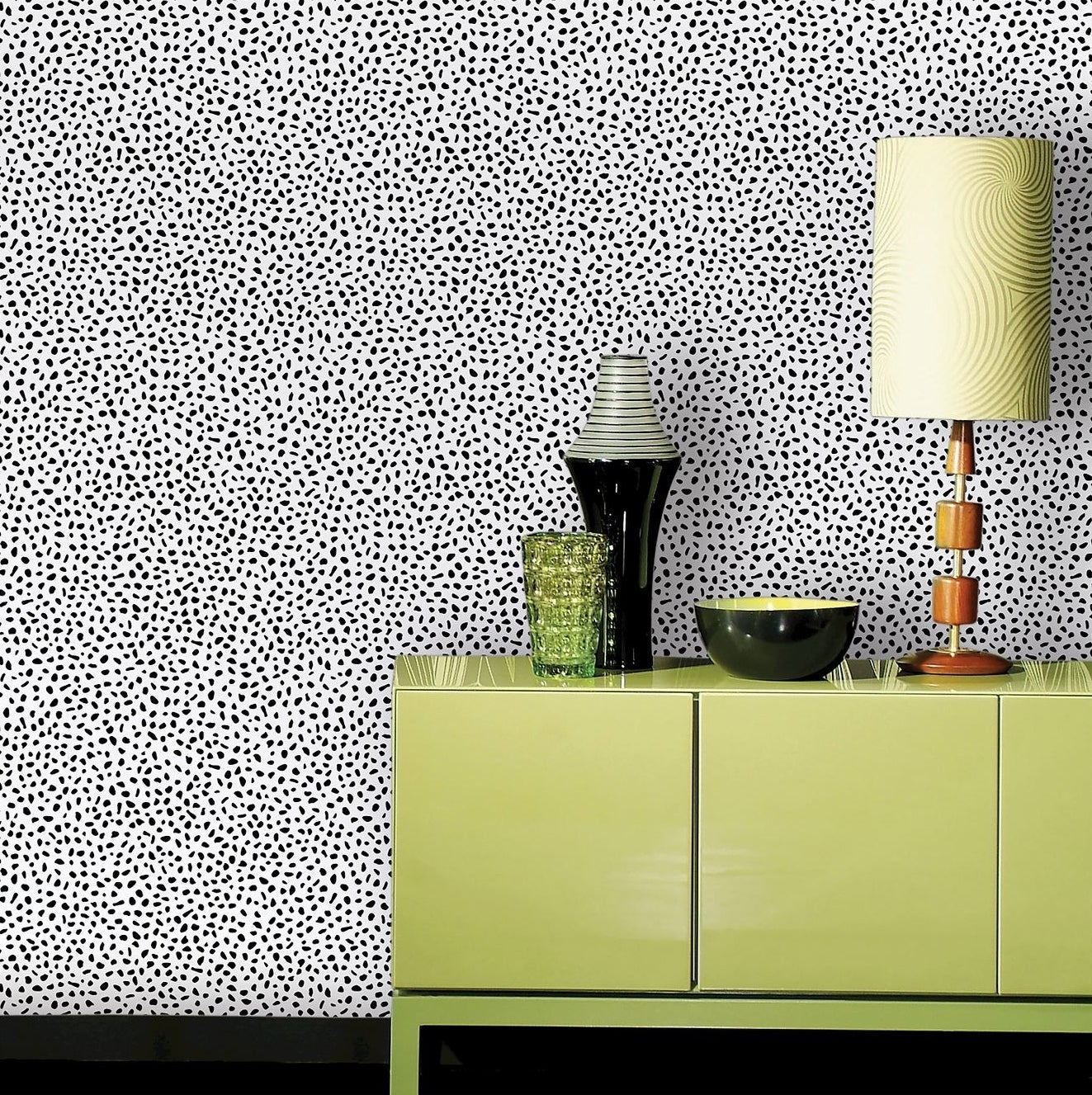 dotted wallpaper on a wall with green furniture in front of it
