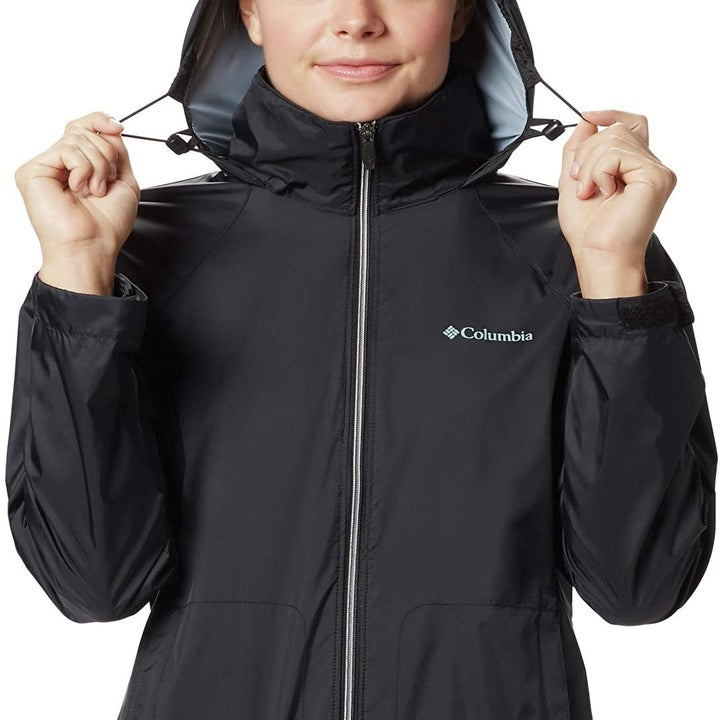 A model wearing the coat in black and showing how the hood is adjustable