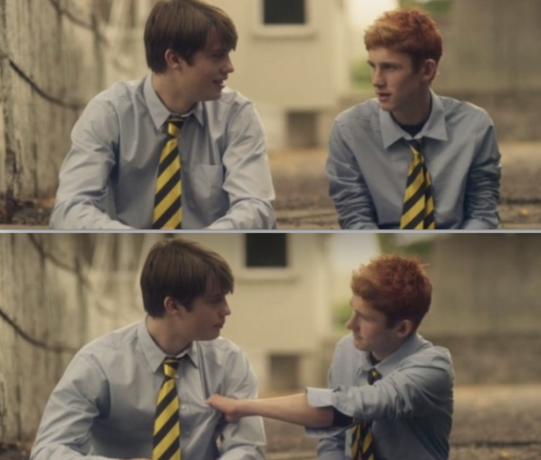 """Ned and Conor sitting together outside in their prep uniforms in """"Handsome Devil"""""""