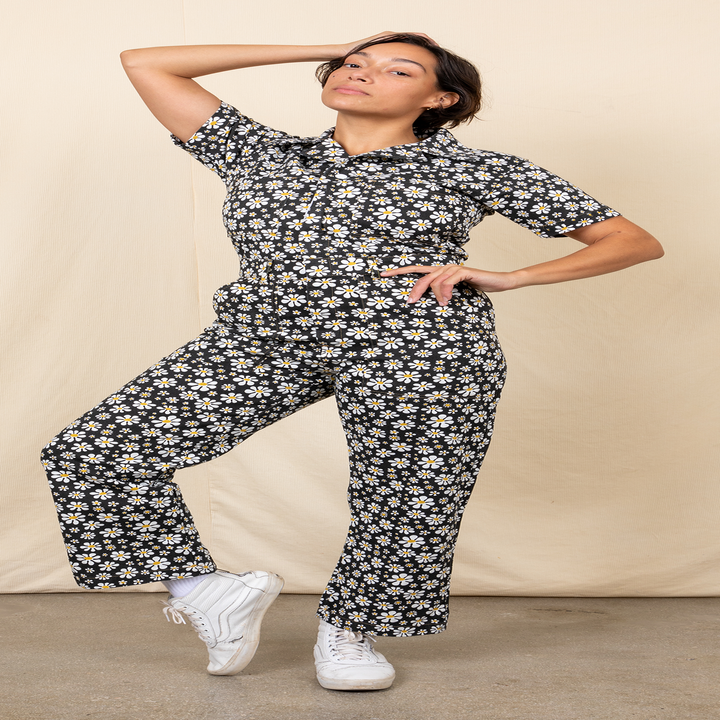 A model wearing the short sleeve jumpsuit in black lazy daisy