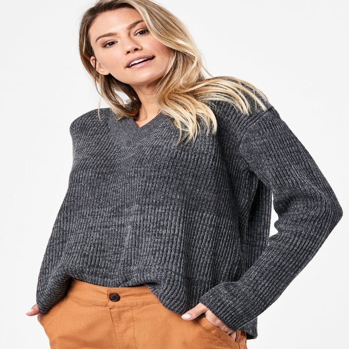 Front view of a model wearing the V-neck sweater in charcoal heather