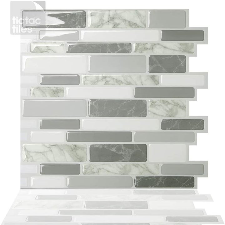 The backsplash with various colors of gray, marble, and ivory tiles