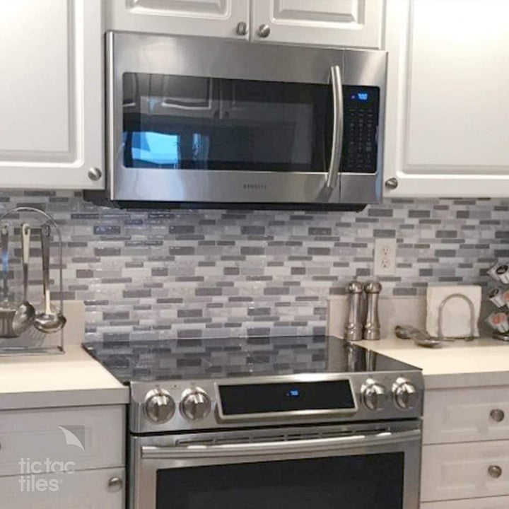 A kitchen with a tiled backsplash installed on the wall