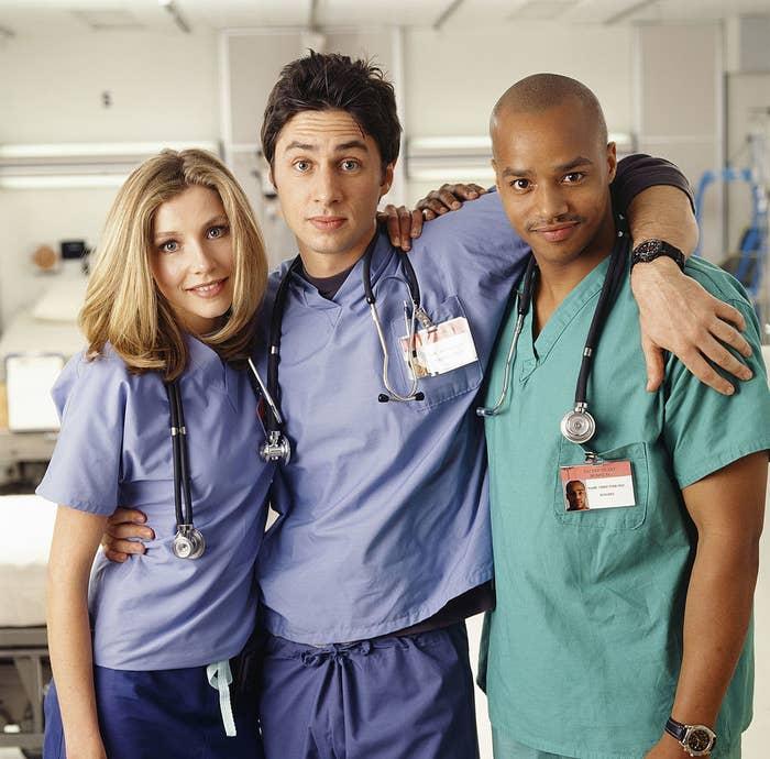 "Sarah Chalke, Zach Braff, and Donald Faison posing on the set of ""Scrubs"" during Season 1"