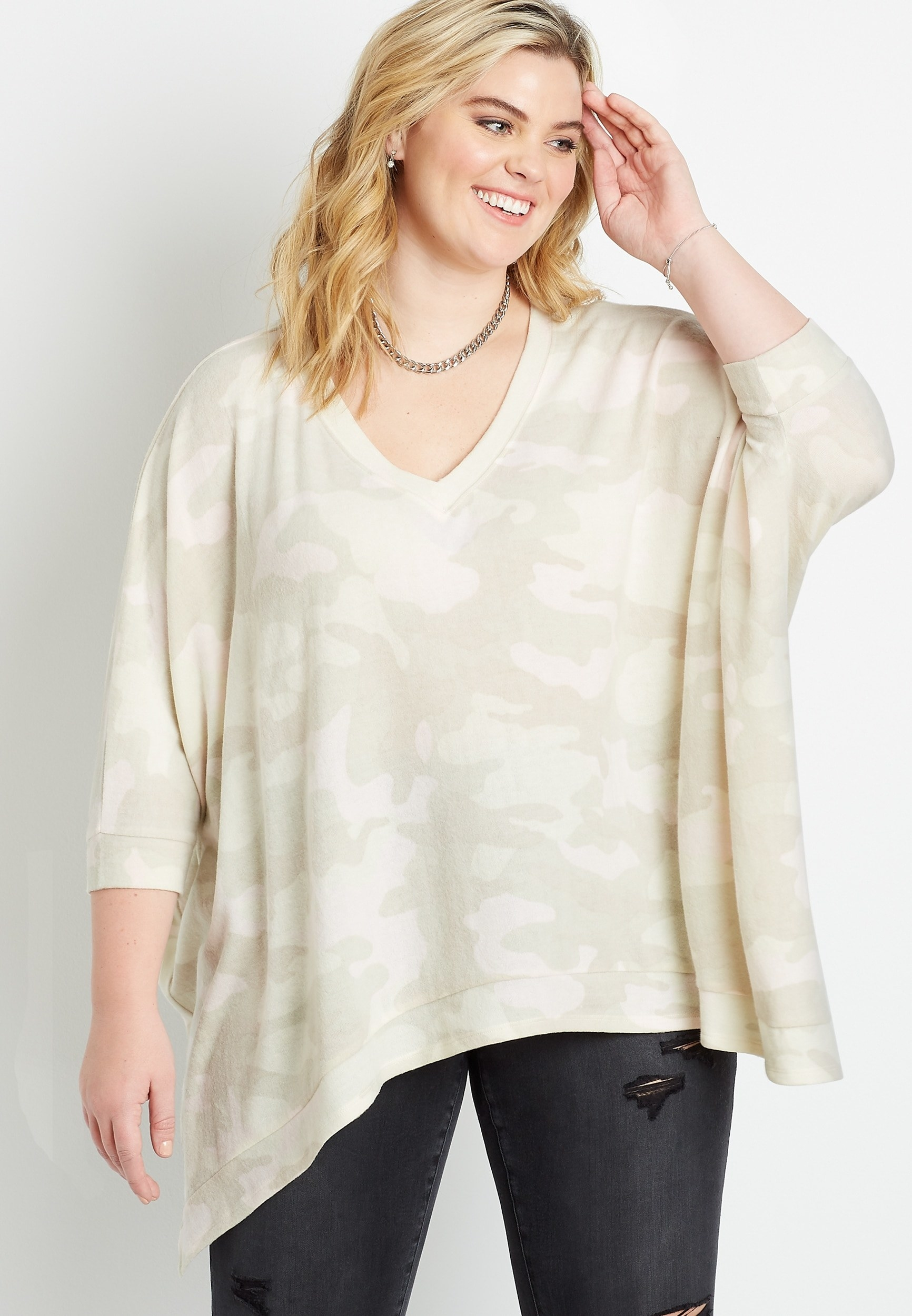 model wearing the poncho in white and beige camo