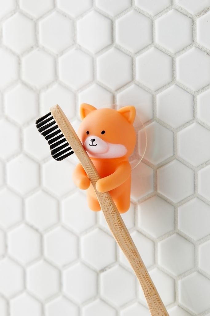 A small corgi shaped toothbrush holder suctioned to a tiled wall