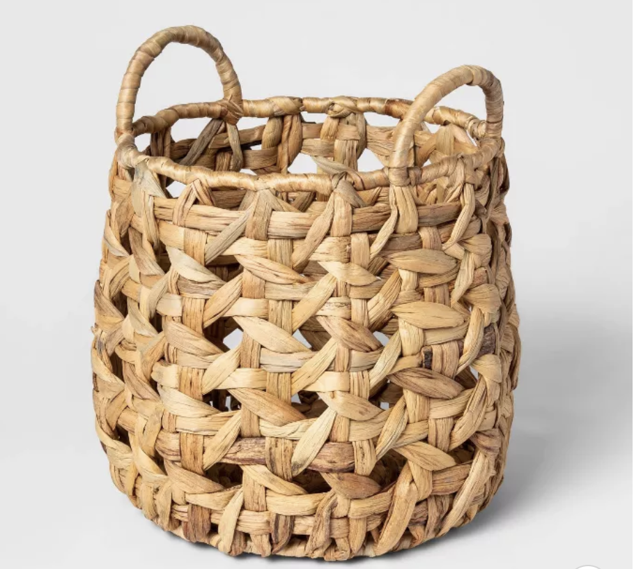 A round woven basket in a beige brown with handles
