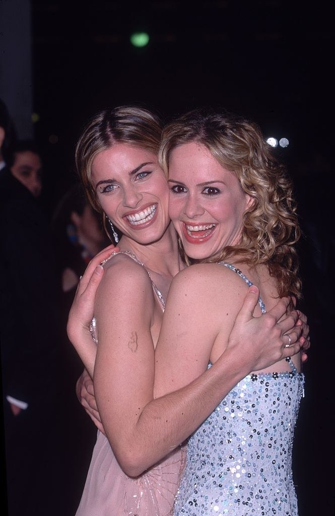 """Sarah Paulson and Amanda Peet hugging each other on a red carpet for """"The Whole Nine Yards"""""""