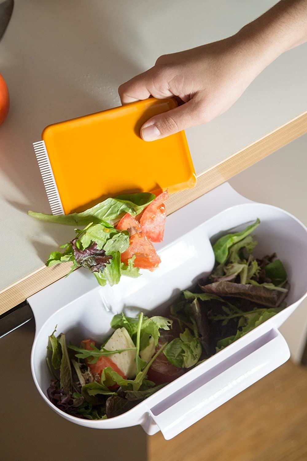 A person scraping kitchen scraps into the over-the-cabinet trap