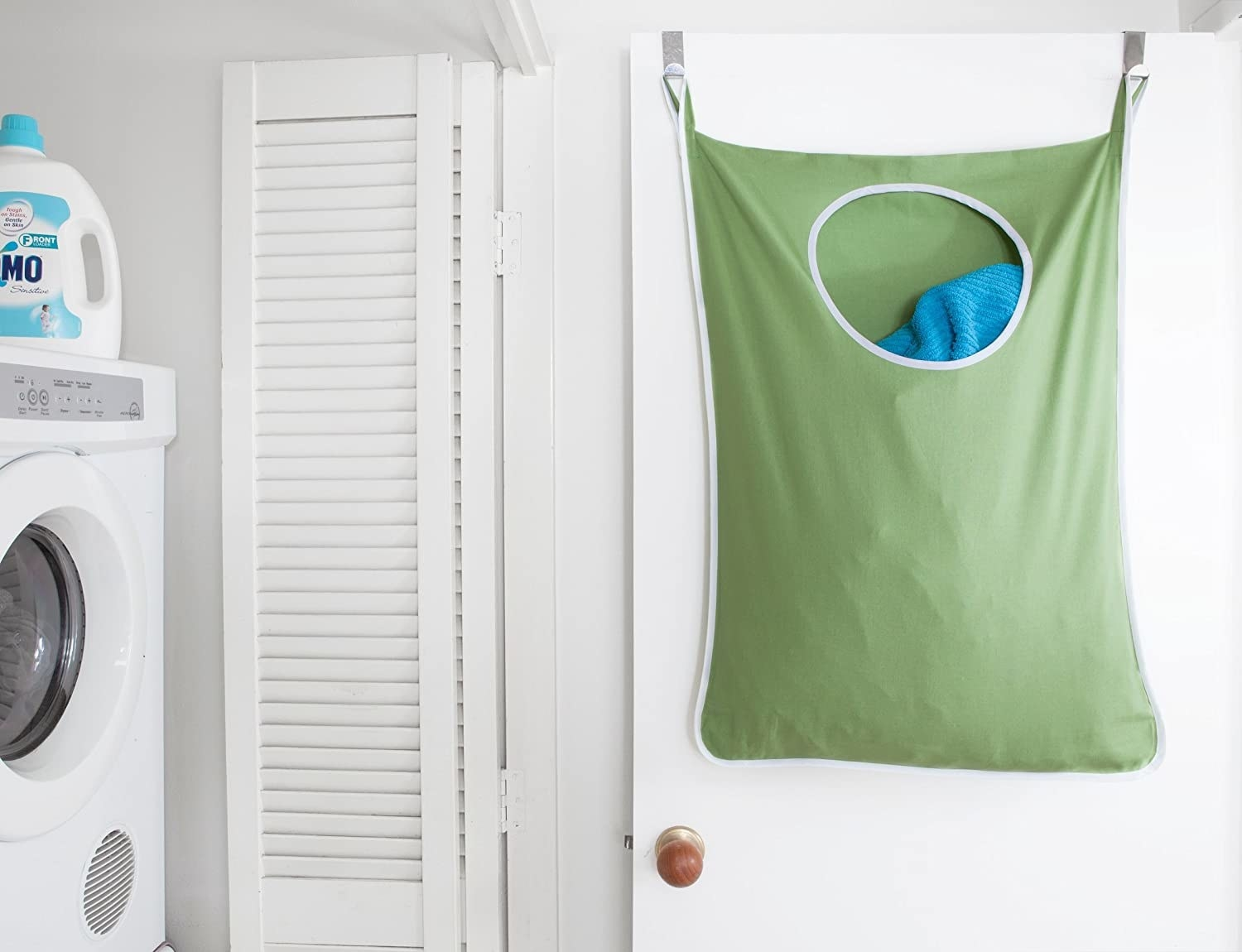 hamper bag hanging on back of laundry room door with circular opening at top for putting in the dirty clothes