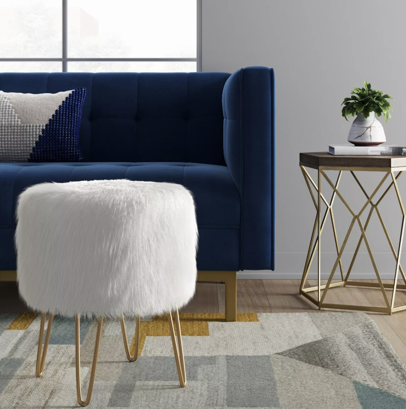 A white faux fur ottoman with gold legs