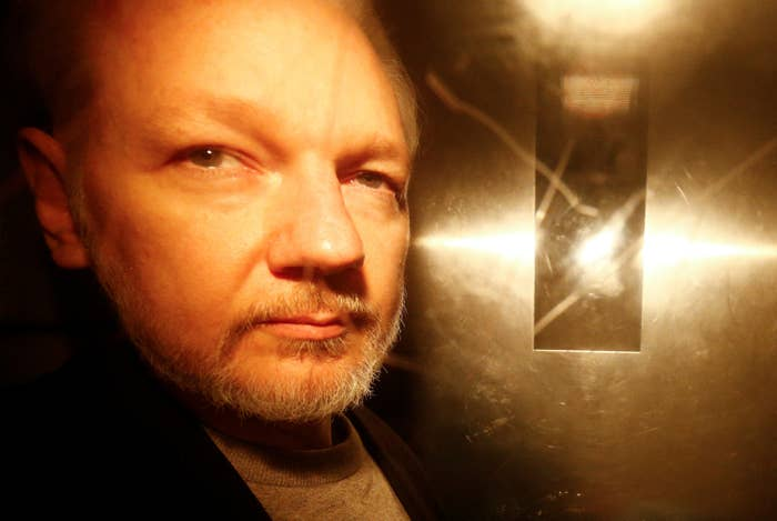 A close-up of Julian Assange's face with the camera's flash reflected in the steel door behind him