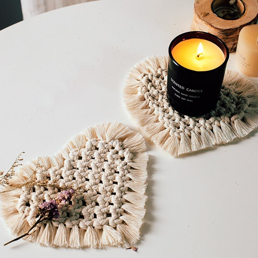 two heart-shaped macrame coasters with fringe around the outsides