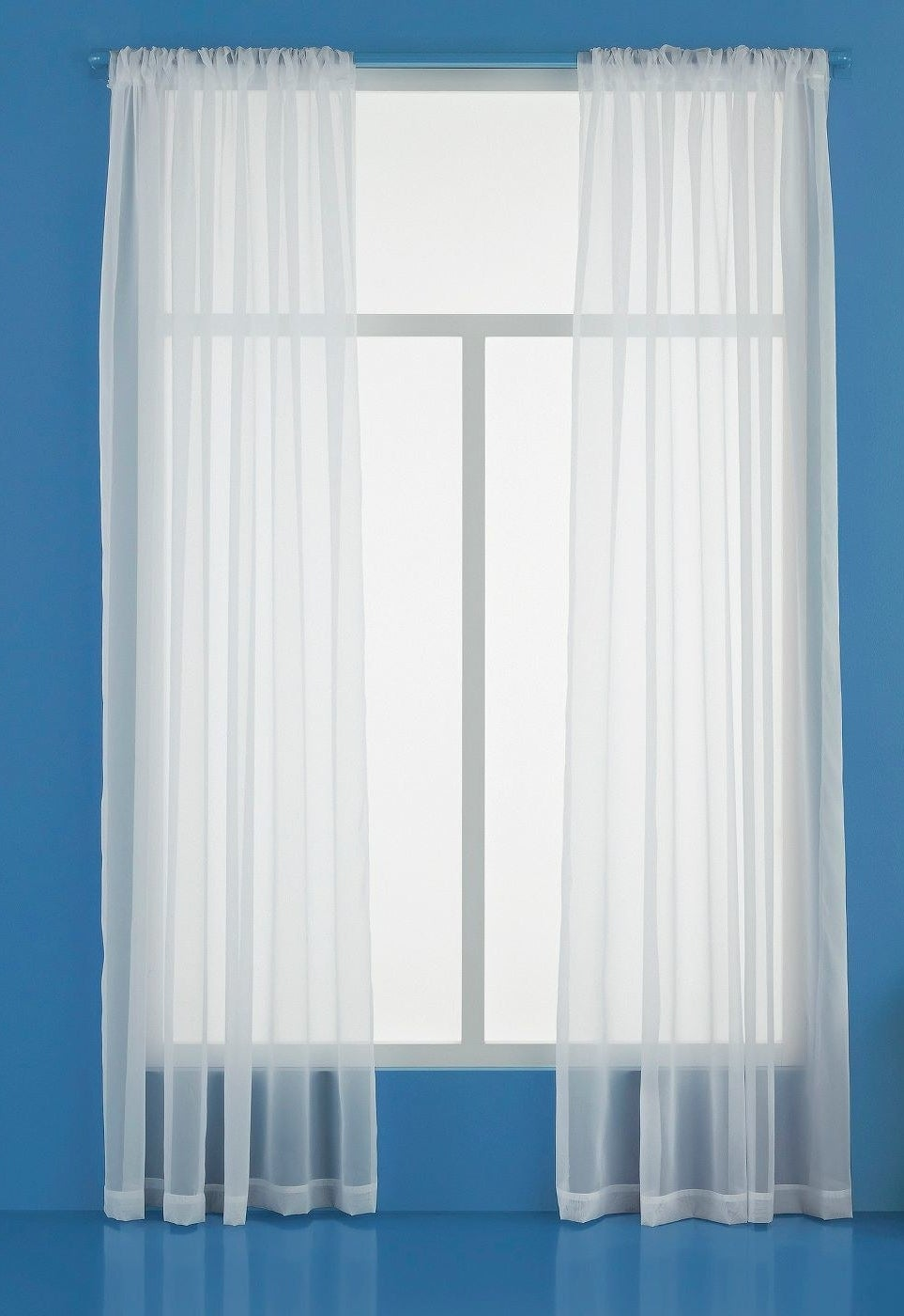 two sheer panel curtains over a window