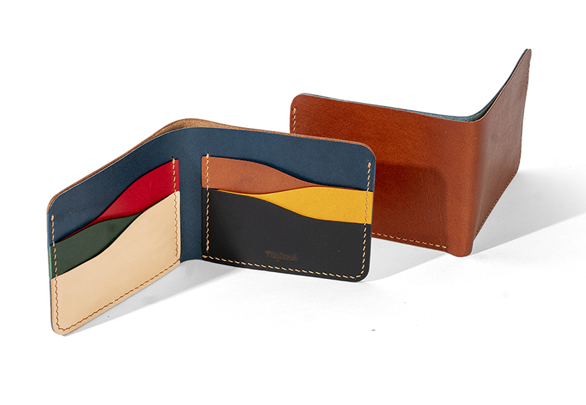 the wallet open showing the different colored card pockets inside and another wallet next to it facing the other way, showing the brown outside
