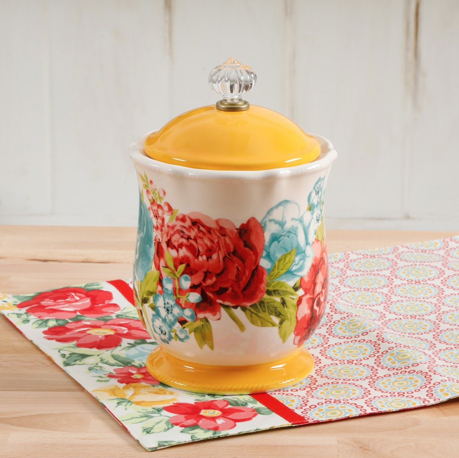 The canister with red and blue flowers and a yellow top